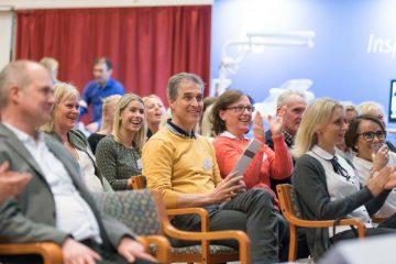 Människor som sitter i publiken och applåderar på tandvårdsdagen